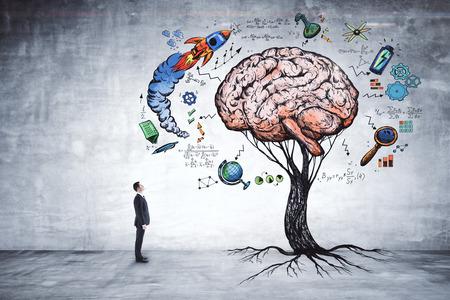 Foto de Businessman looking at abstract brain tree in concrete interior. Education, growth, brainstorm and startup concept  - Imagen libre de derechos