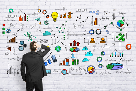 Foto de Back view of young businessman on brick wall background with business sketch. Research and finance concept  - Imagen libre de derechos
