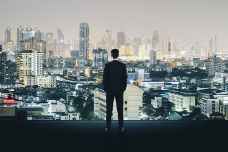 Back view of young businessman on rooftop looking at illuminated night city. Research and tomorrow concept