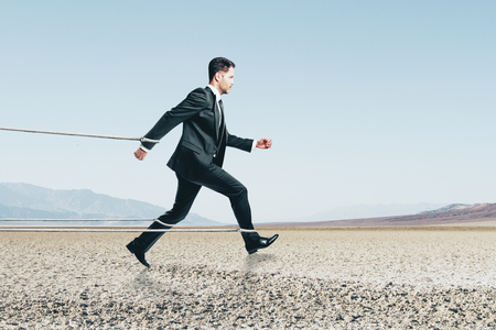 Foto de Side view of running tied businessman on desert background. Effort and success concept - Imagen libre de derechos