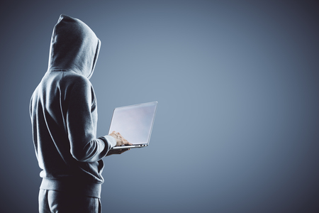Foto de side view on hacker in grey hoody with laptop at grey background. 3D render - Imagen libre de derechos