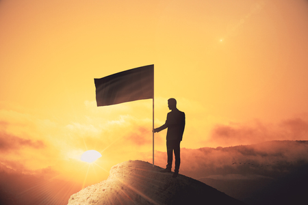 Photo pour Backlit man with flag standing on cliff. Sunset background. Leadership and winner concept - image libre de droit