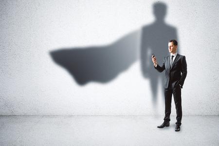 Foto de European businessman with super hero cape shadow standing on concrete wall background. Leadership and security concept - Imagen libre de derechos