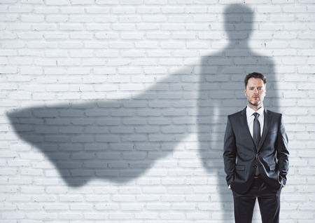 Photo for European businessman with super hero cape shadow standing on brick wall background. Leadership and success concept - Royalty Free Image