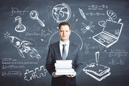 Photo pour Businessman holding books on chalkboard background with business sketch. Education and finance concept - image libre de droit