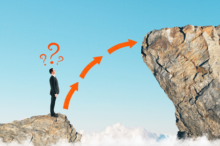 Foto de Side view of young businessman on small cliff thinking how to get onto big one. Career development and growth concept - Imagen libre de derechos