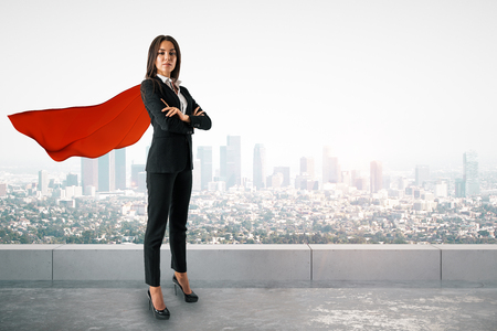 Foto de Attractive young european woman with red hero cape and folded arms standing on city background. Superhero and leader concept - Imagen libre de derechos