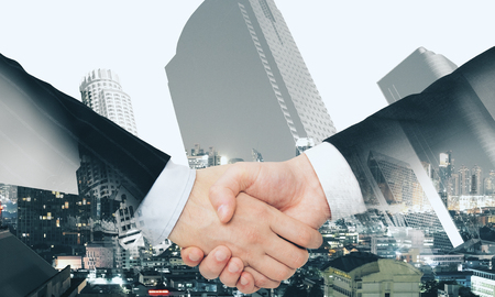 Photo pour Close up of handshake on abstract city background. Teamwork and union concept. Double exposure - image libre de droit
