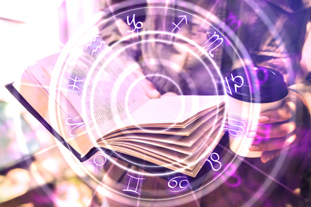 Photo pour Close up of hands holding abstract book with zodiac wheel. Magic and astrology concept. Double exposure - image libre de droit