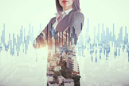 Foto de Attractive young european businesswoman standing on abstract city background with forex chart. Job and investment concept. Double exposure - Imagen libre de derechos