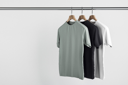 Foto de Empty grey, white and black tees on hanger. Concrete wall background. Design, store and style concept. Mock up, 3D Rendering - Imagen libre de derechos