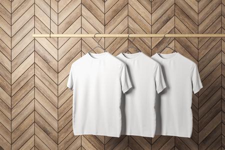 Foto für Empty three white tshirts on hanger. Wooden tile wall background. Design, store and style concept. Mock up, 3D Rendering - Lizenzfreies Bild