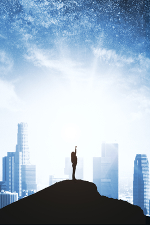 Foto de Confident backlit superhero on hill and starry sky and city background. Purpose and confidence concept - Imagen libre de derechos