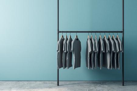 Foto de Hanger with row of tshirts in interior with empty copyspace on blue wall. Design, fashion and ad concept. Mock up, 3D Rendering - Imagen libre de derechos