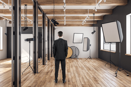 Photo for Back view of young businessman in photo studio with professional equipment, wooden floor and daylight. - Royalty Free Image
