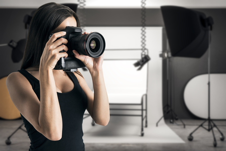 Photo for Young businesswoman taking photo in professional studio. Job and hobby concept. - Royalty Free Image