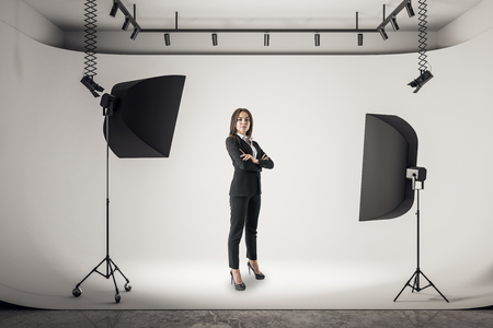 Photo for Attractive young businesswoman with folded arms standing in white photo studio with professional equipment. - Royalty Free Image