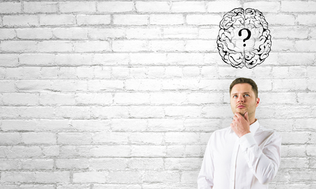Foto de Thoughtful young businessman standing on white brick wall background with brain and question mark sketch. Brainstorm and confusion concept - Imagen libre de derechos