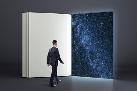 Photo pour Businessman entering abstract open book into open space. Mystery and success concept. - image libre de droit