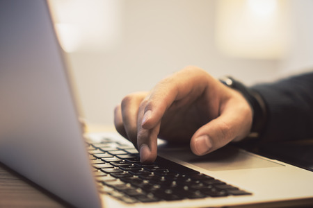 Foto für Side view of man hands using notebook keyboard on wooden desk top workplace. Blurry background. Education, communication, programming and software concept - Lizenzfreies Bild