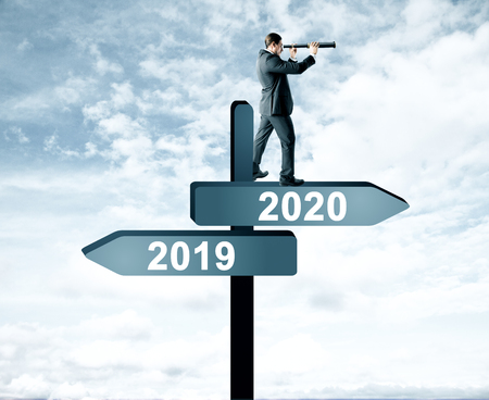 Foto de Side view of attractive man with telescope standing and looking into the distance on abstract year 2019, 2020 direction sign board on sky background. Happy New Year, research and future concept - Imagen libre de derechos