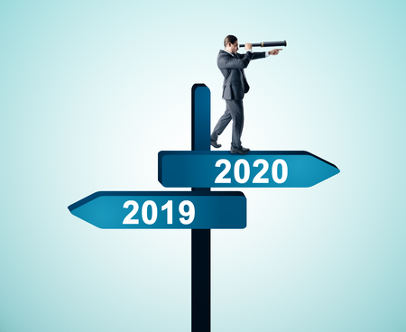 Photo pour Side view of attractive businessman with telescope standing and looking into the distance on abstract year 2019, 2020 direction sign board on sky background. Happy New Year, research and success concept - image libre de droit
