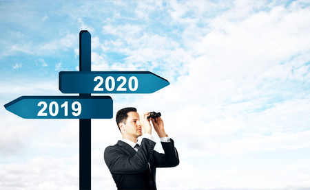 Photo pour Businessman looking into the distance on abstract background with seas2019, 2020  sign post. New Year and future concept - image libre de droit