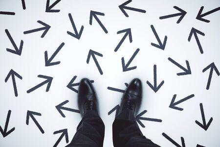 Foto de Top view of businessman feet with arrows on grey background. - Imagen libre de derechos