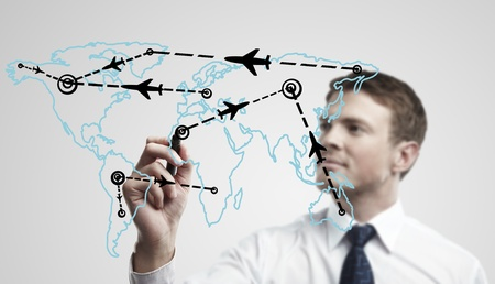 Young business man drawing an airplane routes on world map. Man drawing world map with aircraft flying on a glass window. The metaphor of international air travel around the world, travel to anywhere on the planet Earth and the workload of air traffic