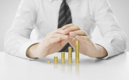 businessman hands covering coin graph