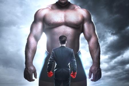 businessman boxing against a big muscular man