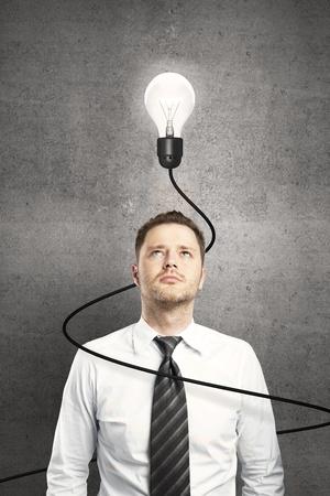 Photo pour businessman and lamp with cable on concrete background - image libre de droit