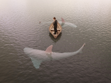 Foto de man thinking  boat with sharks around him - Imagen libre de derechos