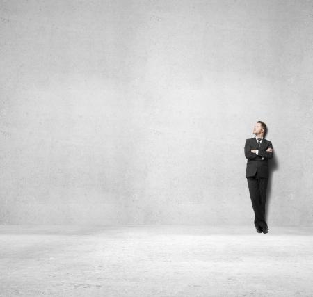 Photo pour businessman standing on concrete room - image libre de droit