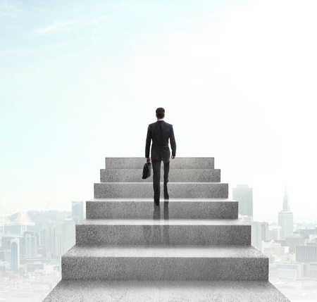 Foto de businessman climbing to stairs on city background - Imagen libre de derechos