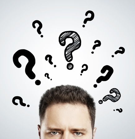 Foto de man with questions symbol over head on gray background - Imagen libre de derechos
