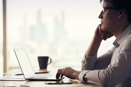 Sideview of thinking caucasian businessman sitting at office desk with laptop, smartphone and coffee cup on blurry city background
