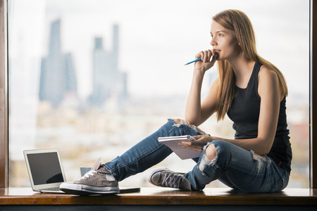 Foto de Thoughtful young woman with notepad in hand sitting on windowsill with blank laptop screen. Blurry city view in the background. Mock up - Imagen libre de derechos