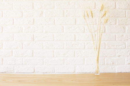 Photo pour Front view of wheat spikes on wooden desktop and white brick background. Mock up - image libre de droit