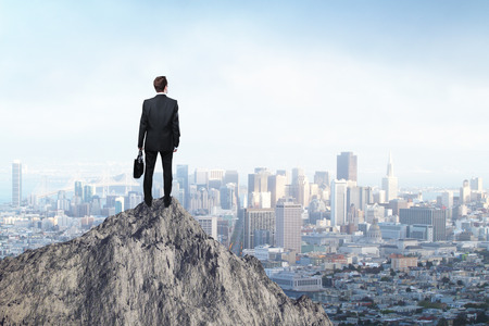 Photo pour Research concept with businessman standing on mountain top and looking at city - image libre de droit