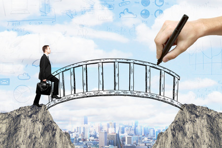 Foto de Success concept with hand drawing bridge over gap between two cliffs and businessman walking across it on city background with business sketches - Imagen libre de derechos