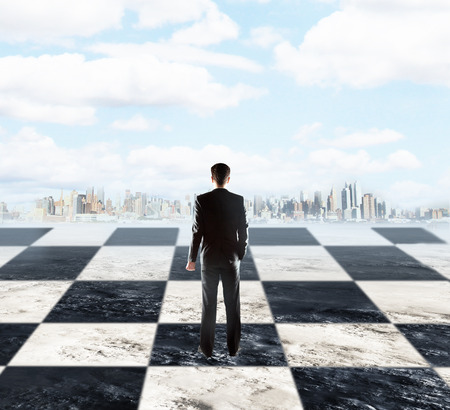 Foto für Strategic planning concept with businessman standing on chessboard and looking at city on sky background with clouds - Lizenzfreies Bild