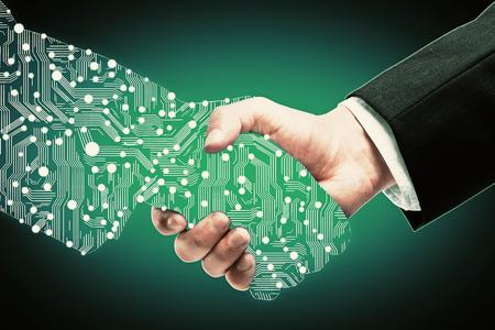 Photo pour Businessman shaking digital partners hand on green background - image libre de droit