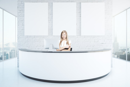 Photo for Cheerful businesswoman at reception desk with three blank posters in interior with white brick wall, shiny floor and panoramic windows with city view. Mock up, 3D Rendering - Royalty Free Image