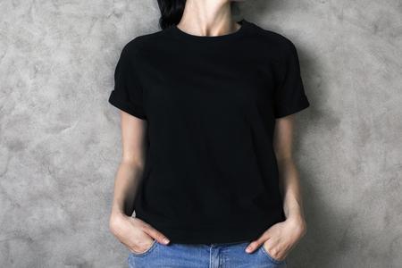 Foto de Girl in plain black shirt and jeans on concrete backgroud. Mock up - Imagen libre de derechos