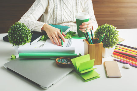Foto de Girl hodling green coffee cup and writing in spiral notepad placed on creative desktop with various items - Imagen libre de derechos