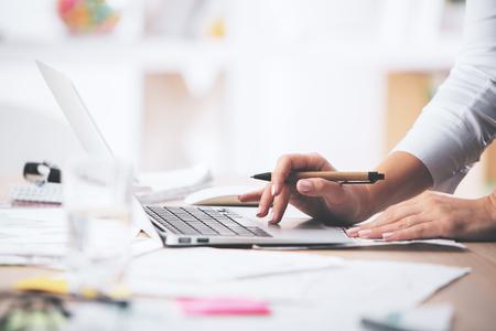 Foto de Side view of businesswoman's hands using laptop computer placed on messy office desktop - Imagen libre de derechos