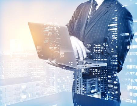 Foto de Businessman using laptop on city background. Double exposure. Communication concept - Imagen libre de derechos