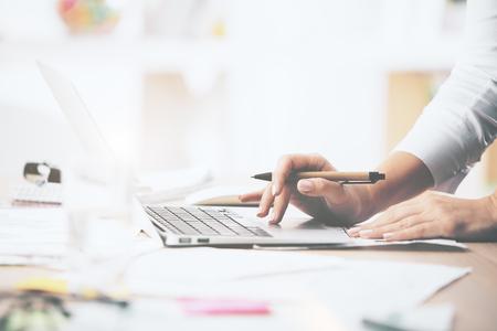 Foto de Close up of female hands using notebook placed on messy office desktop - Imagen libre de derechos