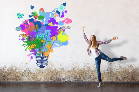 Photo pour Happy european girl in grungy concrete room with creative lamp and spaceship sketch. Successful startup idea - image libre de droit